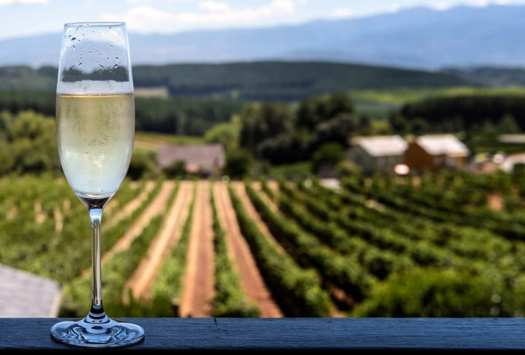A glass of cava with a beautiful winery on the backdrop.
