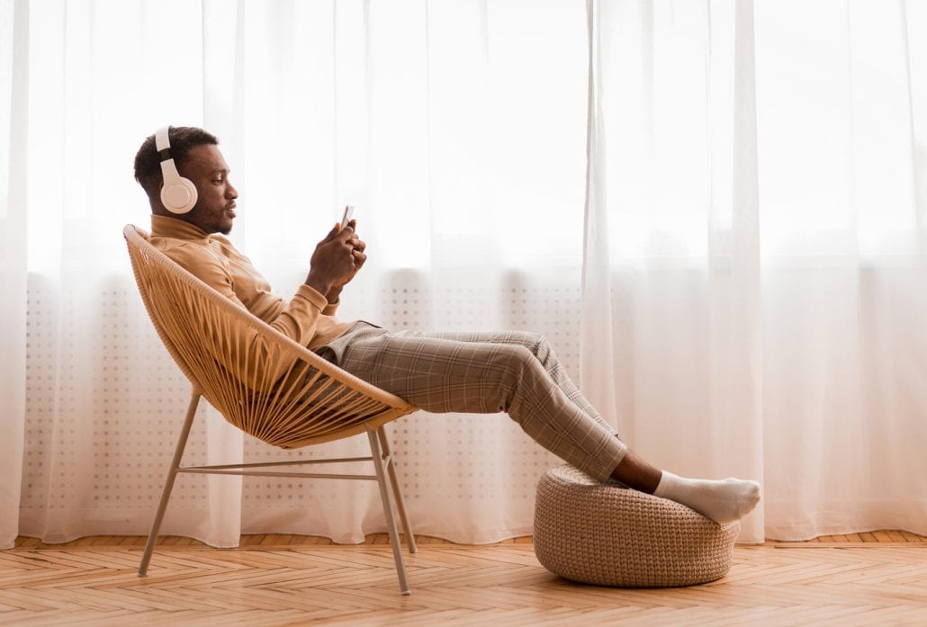 Relaxed Man Listening To Podcast Sitting On Modern Chair Against Window Indoor