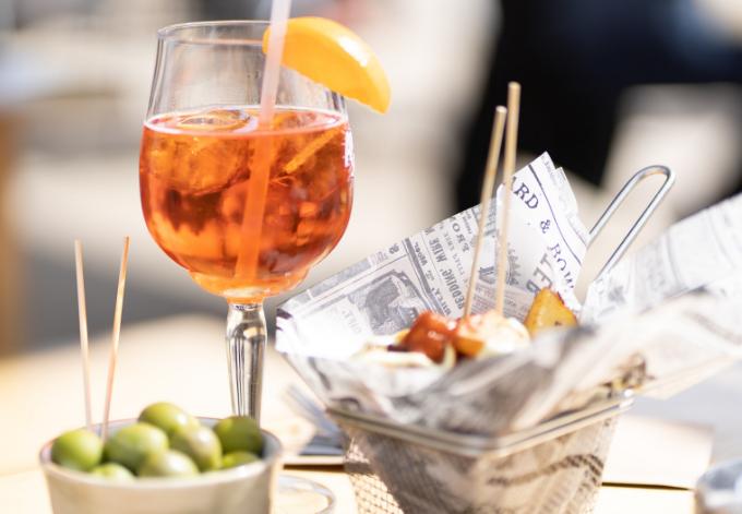 A glass o sangria, a portion of olives and a portion of patatas bravas.