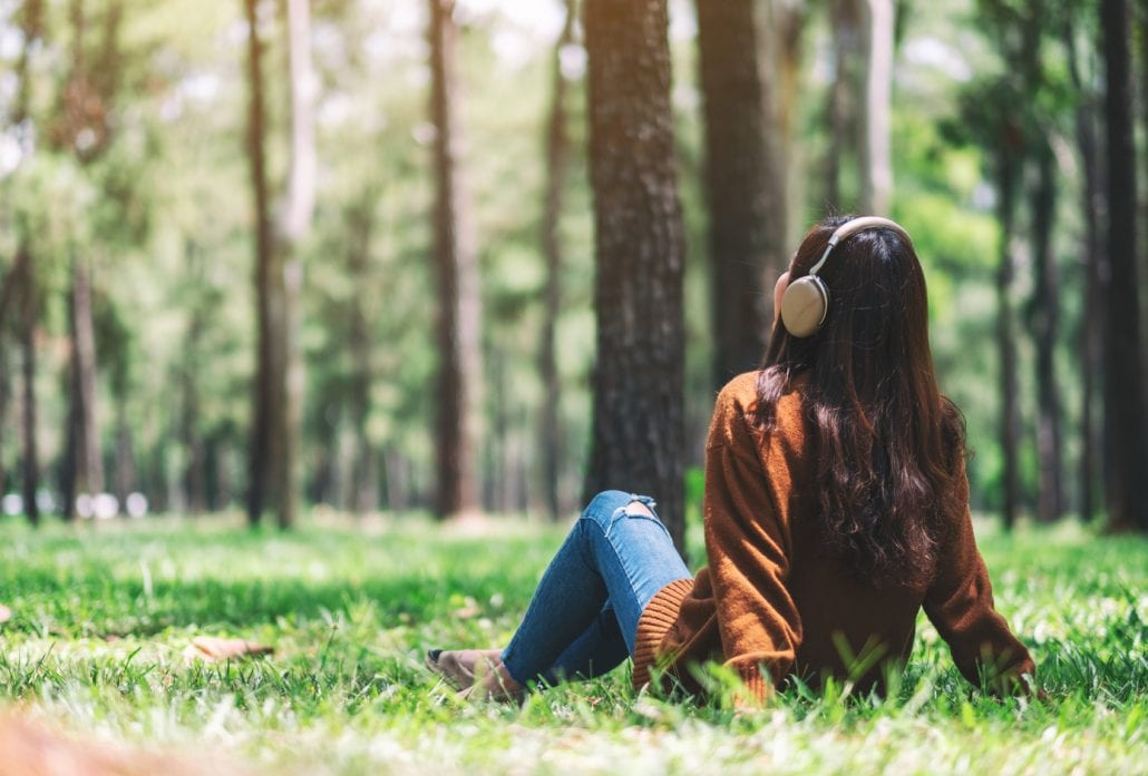 Young woman listening to music with headphones on while sitting at the grass at a park.