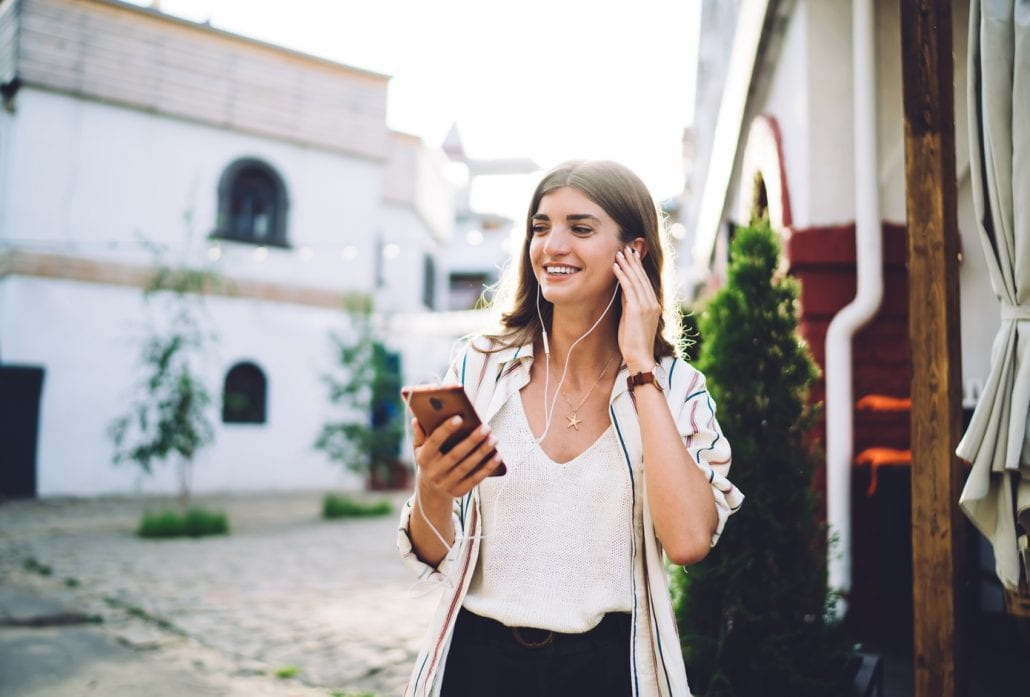 Smiling girl in earphones listening to music on her smartphone.