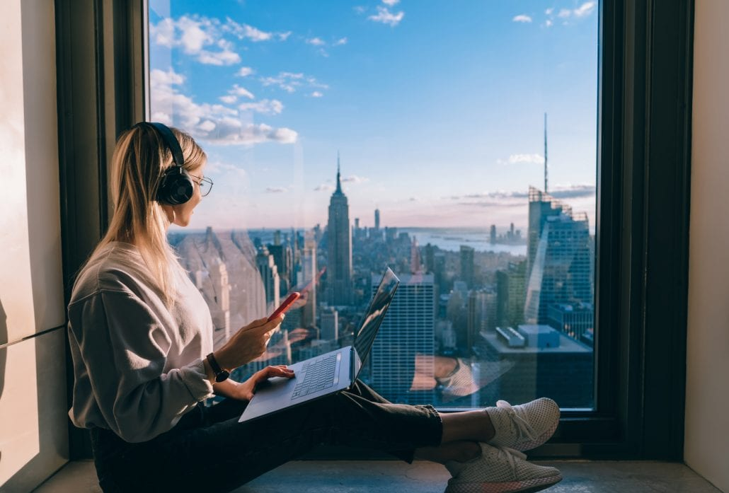 Blond woman with headphones on, a laptop on her lap, sitting on the windowsill and looking at New York's skyline.
